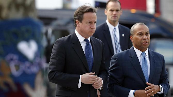 British Prime Minister David Cameron, left, and Massachusetts Gov. Deval Patrick, right, arrive for a visit at the makeshift memorial to the Boston Marathon bombing victims in Copley Square in Boston, Tuesday, May 14, 2013. (AP Photo/Michael Dwyer)