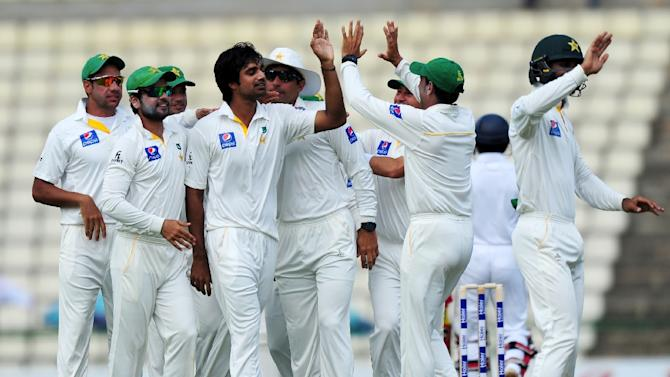 Pakistan's Rahat Ali (C) is congratulated by teammates after dismissing Sri Lankan batsman Kaushal Silva during the opening day of their third and final Test, at the Pallekele International Cricket Stadium, on July 3, 2015