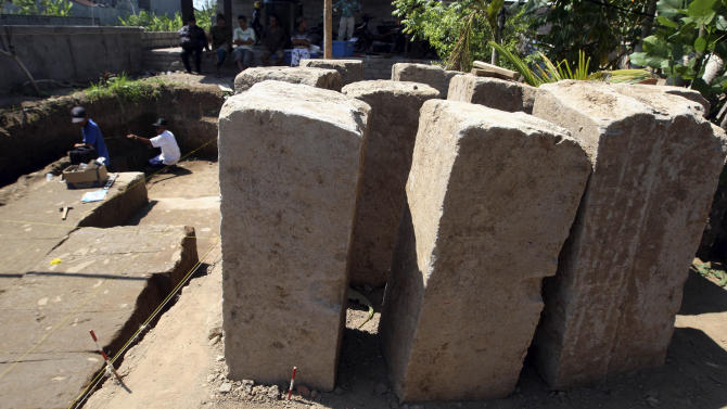 Balinese archaeologists work next to discovered stone structure of an ancient temple in Denpasar, Bali, Indonesia on Friday, Oct. 26, 2012.  An archaeologist says a structure that is believed to be the remains of an ancient Hindu temple has been unearthed on Indonesia's resort island of Bali. (AP Photo/Firdia Lisnawati)