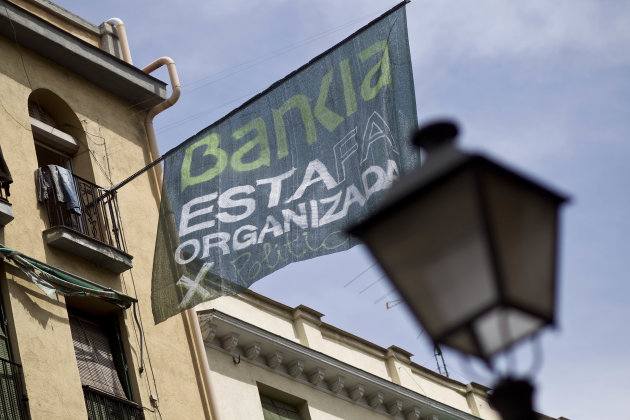 A banner reading in Spanish 'Bankia Organized Fraud' hangs from a window of a recently occupied Bankia bank's building, in Madrid, Spain, Sunday, June 3, 2012. Spain will stick to harsh austerity measures until it emerges from financial crisis, Prime Minister Mariano Rajoy said yesterday, promising that the country would survive the present economic turmoil. (AP Photo/Alberto Di Lolli)