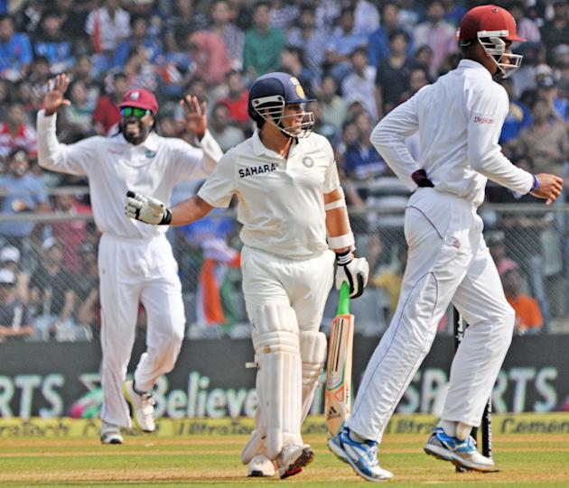 West Indian players celebrate as master blaster Sachin Tendulkar walks back to pavilion after scoring 74 runs during the 2nd day of the 2nd Test Match between India and West Indies at Wankhede Stadium