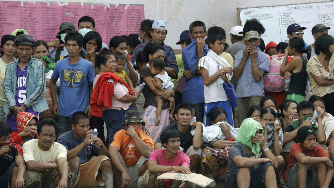 Flash flood victims wait for relief supplies at an evacuation center following Tuesday's devastating typhoon, in New Bataan township, Compostela Valley in the southern Philippines, Thursday, Dec. 6, 2012.  The powerful typhoon that washed away emergency shelters, a military camp and possibly entire families in the southern Philippines has killed hundreds of people with nearly 400 missing, authorities said Thursday. (AP Photo/Bullit Marquez)