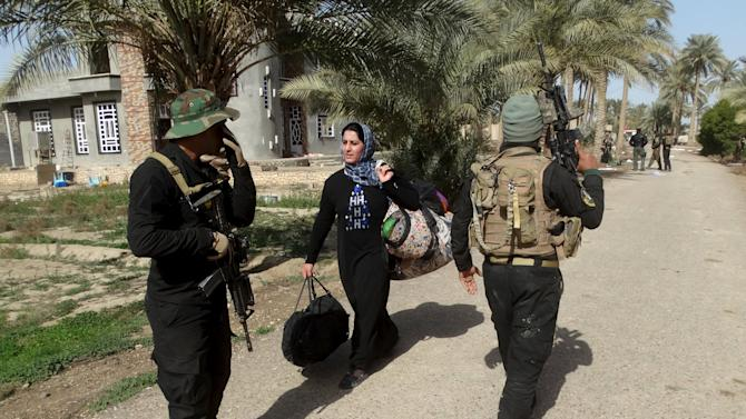 Iraqi security forces stand guard while civilians flee to a safe area with help from Iraqi security forces in Ramadi city