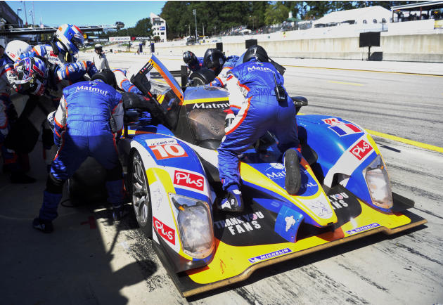 ORECA Peugeot driver Nicolas Lapierre, left, of France, gives the car to teammate Marc Gene, second from left, of Spain, during a pitstop in the American Le Mans Series' Petit Le Mans auto race at Roa