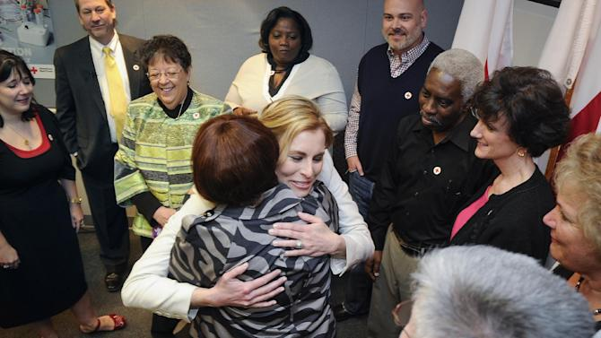 IMAGE DISTRIBUTED FOR AMERICAN RED CROSS- Supermodel Niki Taylor, center, hugs Debora Curl during a surprise reunion and opportunity to thank some of the American Red Cross volunteer blood donors who helped save her life following a 2001 car accident, held Wednesday, March 20, 2013, in Atlanta. The American Red Cross is known for providing humanitarian aid around the world, and  supplies around 40 percent of the nation's blood, relying on volunteers and the generosity of the American public to perform its mission. (John Amis/AP Images for American Red Cross)