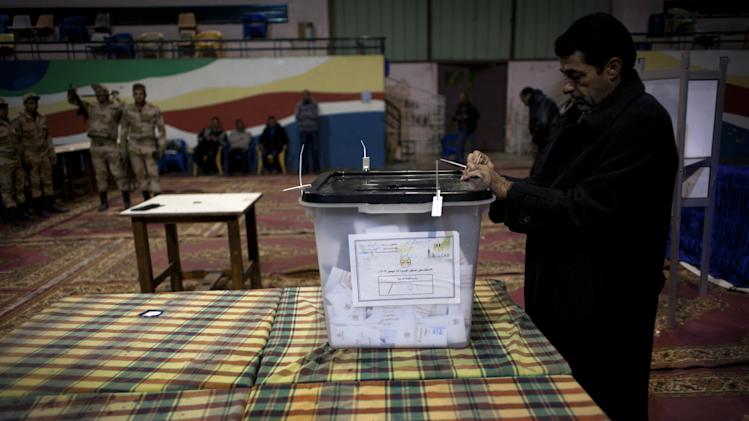 An Egyptian election worker controls a ballot box ahead of the counting process at the end of the second round of a referendum on a disputed constitution drafted by Islamist supporters of president Mohammed Morsi at a polling station in Giza, Egypt, Saturday, Dec. 22, 2012. Egypt's Islamist-backed constitution headed toward likely approval in a final round of voting on Saturday, but the deep divisions it has opened up threaten to fuel continued turmoil. (AP Photo/Nasser Nasser)