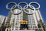 Australian swimmers pose for photos with the Olympic rings at the Athletes' Village at the Olympic Park in east London, on July 22, 2012
