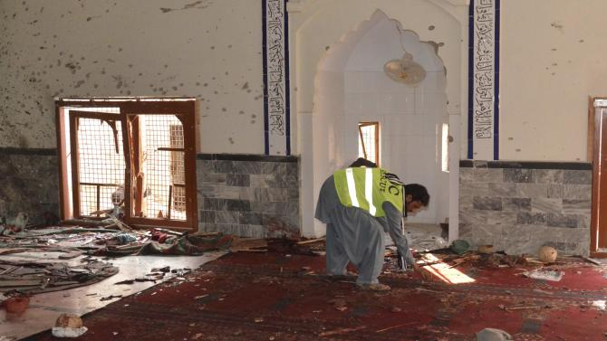 Rescue worker collects evidence after an explosion in a Shi'ite mosque in Shikarpur