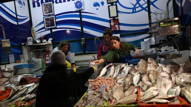 A woman receives a bill after paying for her fish at Lisbon's Ribeira food market, Tuesday, Feb. 11, 2014. Portugal, which uses the shared euro currency, was engulfed by the eurozone's debt crisis and needed an euro 78 billion (US$106.6 billion) rescue in 2011 to avoid bankruptcy as jittery investors deserted it. That money runs out in June, and the government is keen to re-establish access to markets before then. (AP Photo/Francisco Seco)