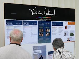 Festivalgoers look at a noticeboard listing details of the day's events at the Verbier Festival