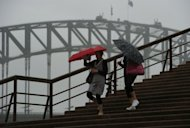 Tourists shelter under umbrellas as they leave the Sydney Opera House on March 2, 2012. Some 1,600 Australians were forced from their homes by flooding Friday, and 22 rescued from rising waters