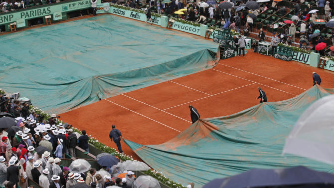 Stadium employees cover center court as the mens final match between Rafael Nadal of Spain and Novak Djokovic of Serbia was suspended because of the rain at the French Open tennis tournament in Roland Garros stadium in Paris, Sunday June 10, 2012. (AP Photo/Christophe Ena)