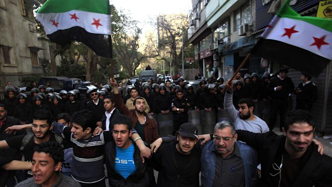 Egyptian and Syrian protesters chant slogans as they protest against Iran's President Mahmoud Ahmadinejad, during his visit to Egypt for the 12th summit of the Organization of Islamic Cooperation, in front of the Iranian diplomatic representation office in Cairo, Egypt, Wednesday, Feb. 6, 2013. (AP Photo/Khalil Hamra)