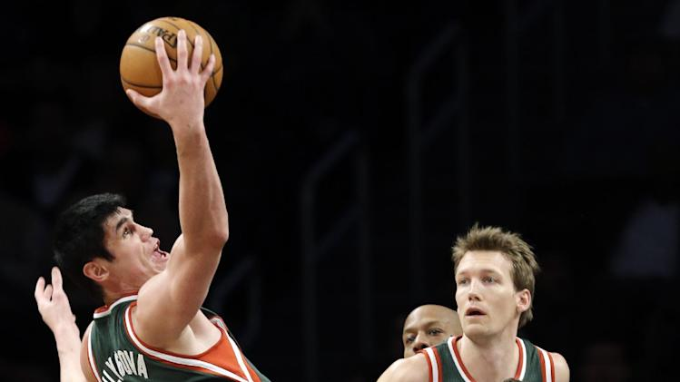 Milwaukee Bucks forward Ersan Ilyasova (7) pulls in a pass as Brooklyn Nets forward Kris Humphries (43) defends in the first half of their NBA basketball game at Barclays Center, Tuesday, Feb. 19, 2013, in New York. (AP Photo/Kathy Willens)