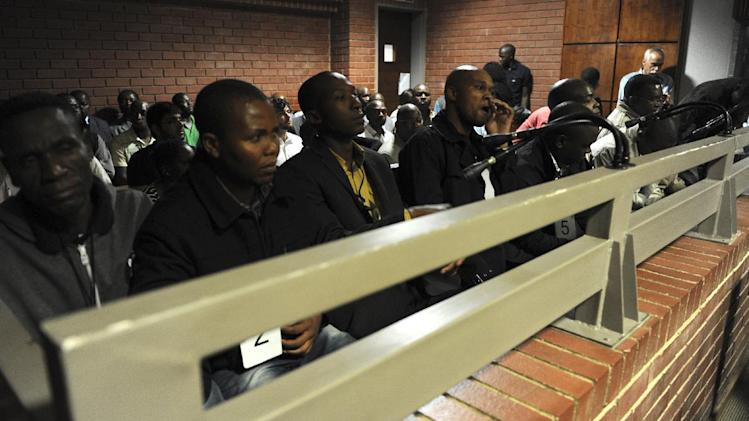 Eight police officers charged with murdering a man who was dragged from a police vehicle last week, sit in the dock before start of their bail hearing in a courthouse in Benoni outside Johannesburg, South Africa, Friday, March 8, 2013. The killing of Mido Macia, a taxi driver from Mozambique who died in police custody on Feb. 27, shocked South Africans and viewers around the world after graphic video footage of him being tied to a vehicle by uniformed officers and dragged down a street was broadcast and posted online. (AP Photo/Werner Beukes/Pool)