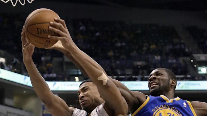 Indiana Pacers guard Orlando Johnson, left, pulls down a rebound in front of Golden State Warriors center Festus Ezeli during the first half of an NBA basketball game in Indianapolis, Tuesday, Feb. 26, 2013. (AP Photo/AJ Mast)