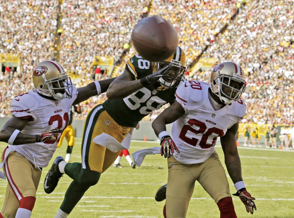 San Francisco 49ers' Donte Whitner (31) and  Perrish Cox (20) break up a pass intended for Green Bay Packers' Jermichael Finley (88) during the first half of an NFL football game Sunday, Sept. 9, 2012, in Green Bay, Wis. (AP Photo/Jeffrey Phelps)