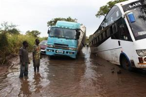 Truck drivers and passengers remain stranded in a flooded section of a road at Nimule