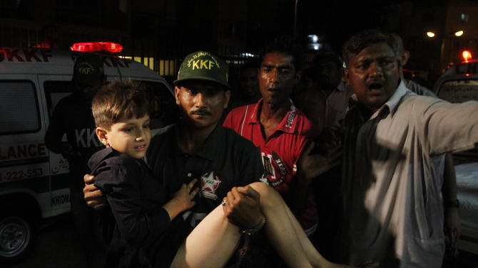 Pakistani volunteers rush an injured boy to hospital following an explosion in Karachi, Pakistan on Friday, April 26, 2013. A bomb planted near the office of a political party threatened by the Taliban has killed many people in southern Pakistan, police said. (AP Photo/Shakil Adil)