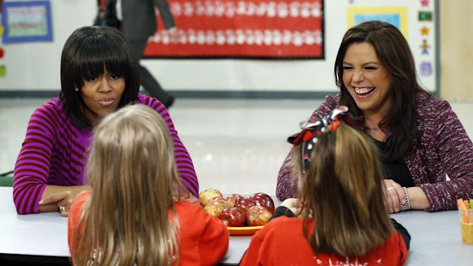 "First lady Michelle Obama and Food Network chef Rachel Ray discuss lunches that students from the Eastside and Northside Elementary Schools receive during a ""Let's Move!"" program at the Clinton, Miss., schools Wednesday, Feb. 27, 2013. The pair visited with the children and conducted a cooking contest between the schools' chefs. (AP Photo/Rogelio V. Solis)"