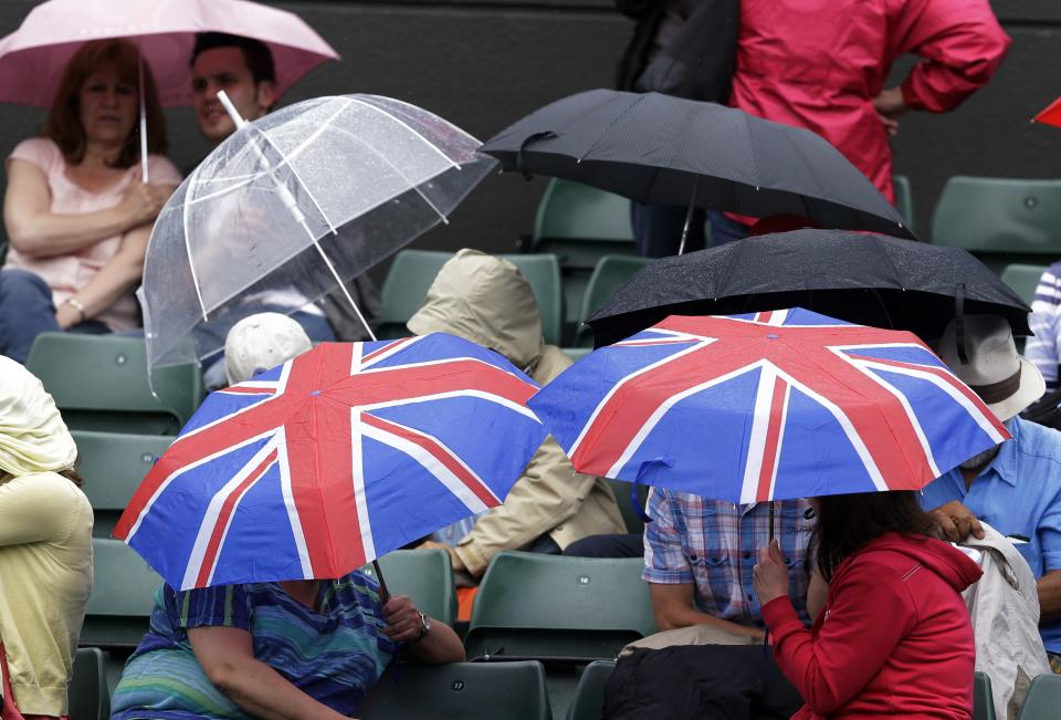 Spectators watch Agnieszka Radwanska of Poland face Maria Kirilenko of Russia in inclement weather during a quarterfinals match at the All England Lawn Tennis Championships at Wimbledon, England, Tuesday, July 3, 2012. (AP Photo/Kirsty Wigglesworth)