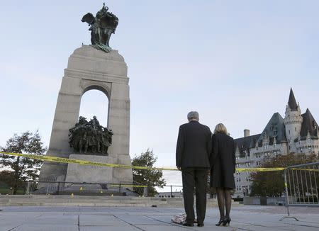 Prime Minister Stephen Harper and his wife Laureen Harper pay their respects to Cpl. Nathan Cirillo at the Canada War Memorial in Ottawa