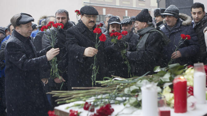 Syrian Ambassador to Russia Riyad Haddad, second left, lays flowers during a memorial action at the Syrian Embassy in Moscow, Thursday, Jan. 17, 2013. Pro-government Syrians and their Russian supporters gathered at the Syrian Embassy in memory of dozens of the Aleppo University's students who died during a terrorist attack. (AP Photo/Misha Japaridze)
