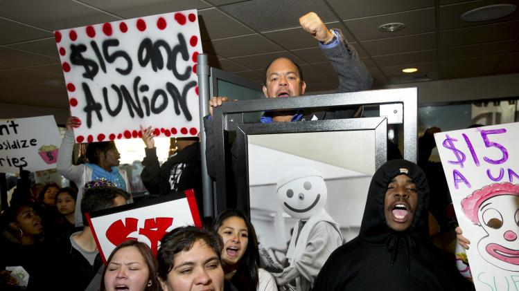 Demonstrators demanding an increase in worker wages protest inside a Jack in The Box fast food restaurant in Oakland
