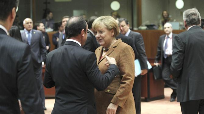 German Chancellor Angela Merkel, center right, speaks with French President Francois Hollande, center left, during a round table meeting at an EU summit in Brussels on Friday, Nov. 23, 2012. EU leaders begin what is expected to be a marathon summit on the budget for the years 2014-2020. The meeting could last through Saturday and break up with no result and lots of finger-pointing. (AP Photo/Yves Logghe)