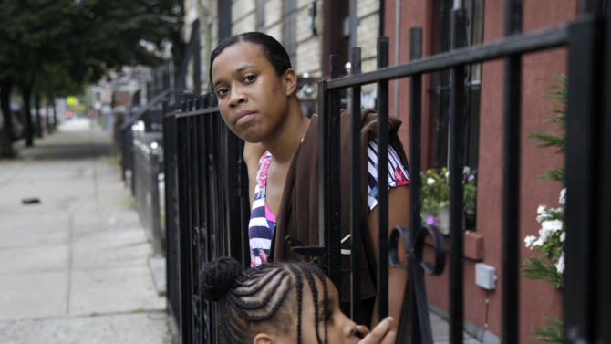 Olgita Blackwood, top, waits for her son to return home from school with her daughter, Malaysia Blackwood, 7, at their apartment in the Drew House in New York, Wednesday, Oct. 3, 2012.  The program, called Drew House, is one of a kind in the nation, where mothers arrested on felonies can live with their children, instead of in prison. The program has been lauded as a success that should be replicated around the country, but the small house is already full, and without additional funding and space, it can't grow.  (AP Photo/Seth Wenig)