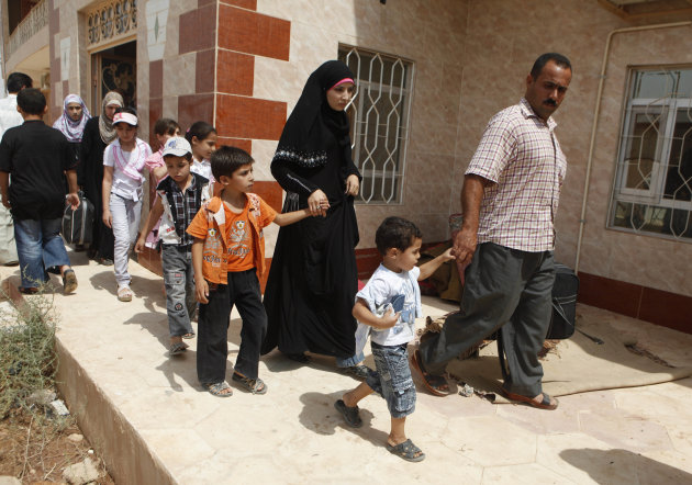 In a Wednesday, July 25, 2012 photo, Iraqi refugees from Syria arrive at the border crossing near the Iraqi town of Qaim, 200 miles (320 kilometers) west of Baghdad, Iraq. Over 15,000 Iraqis have fled the Syrian civil war over the last two weeks. (AP Photo/Karim Kadim)