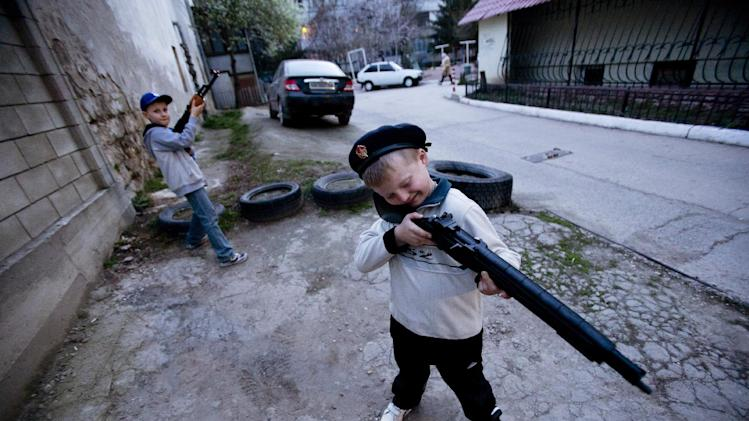 Ukrainian boys play with a toy gun in Simferopol, Crimea, Tuesday, March 25, 2014. (AP Photo/Pavel Golovkin)