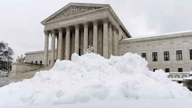 Shoveled snow is piled up at the Supreme Court in Washington, Monday, March 17, 2014, after a St. Patrick's Day snowstorm shut down the federal government and schools. With a harsh winter that closed the federal government, schools and offices for several days this year, Washington and other parts of the U.S. seemed to be getting used to digging out of the snow and cold as yet another storm blew into Mid-Atlantic and up the East Coast on Monday. (AP Photo/J. Scott Applewhite)