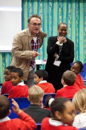 In this image made available  by LOCOG shows Oscar winning director Danny Boyle as he visits  Colegrave Primary School, Newham London  a school selected to audition for the London 2012 Opening Ceremony, Friday Jan. 27, 2012. Boyle offered a sneak peek Friday of his vision for the 2012 London Olympics opening ceremony, revealing that he would ring a massive bell to start the festivities and include a segment on one of Britain's most maligned institutions, the National Health Service. (AP Photo/ Dave Poultney/LOCOG)