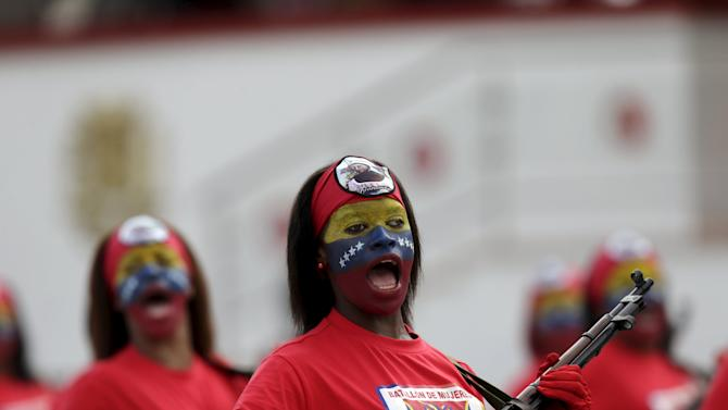Female soldiers with their faces painted in the colours of the Venezuelan flag, march during a military parade to celebrate the anniversary of Venezuela's independence in Caracas