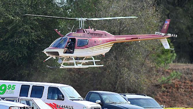 The Dale County Sheriffs Department helicopter lands at the scene of an ongoing hostage crisis in Midland City, Ala., Friday, Feb. 1, 2013.  More than three days after authorities said a gunman shot a school bus driver dead, grabbed a kindergartner and slipped into an underground bunker, the man showed no signs Friday of turning himself over to police. (AP Photo/The Dothan Eagle, Jay Hare)