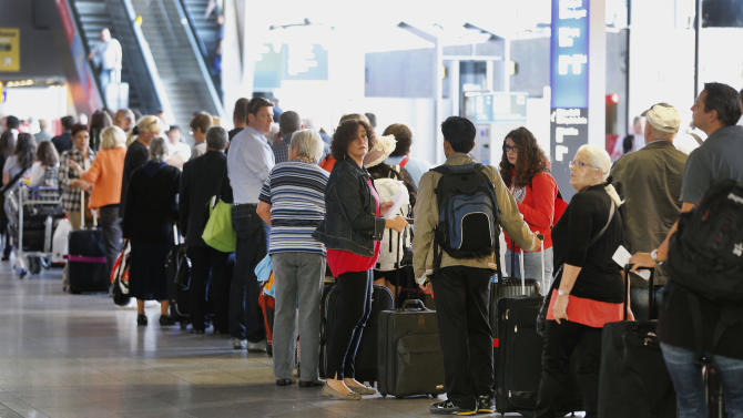 Passengers queue at a terminal during a flight attendant's strike of Lufthansa airline at  Frankfurt airport, Germany, Tuesday, Sept. 4, 2012. A union representing Lufthansa flight attendants escalated a bitter pay dispute on Tuesday, calling members out on strike at three German airports _ including the two biggest, Frankfurt and Munich _ in a showdown with an airline determined to bring down costs in the face of increasingly tough competition. Lufthansa scrapped many short- and medium-haul flights and said it also had to cancel about a third of intercontinental flights at Frankfurt _ among them services to and from destinations including Los Angeles, Houston, Chicago, Beijing and Mexico City. It listed around 200 flights as canceled Tuesday morning, most of them to and from Frankfurt.   (AP Photo/Michael Probst)