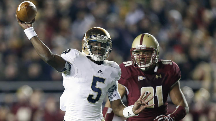 Notre Dame quarterback Everett Golson throws under pressure from Boston College's Kasim Edebali during the first half of an NCAA college football game in Boston Saturday, Nov. 10, 2012. (AP Photo/Winslow Townson)
