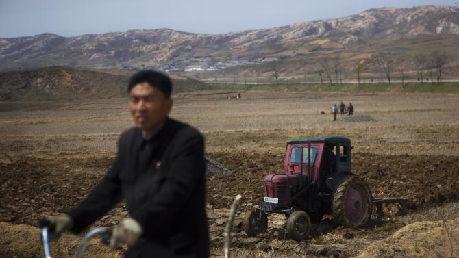 In this April 24, 2013 photo, a North Korean man passes by on a bicycle as a farmer in a tractor works in his field southeast of Kaesong, North Korea near the demilitarized zone that separates the two Koreas. (AP Photo/David Guttenfelder)