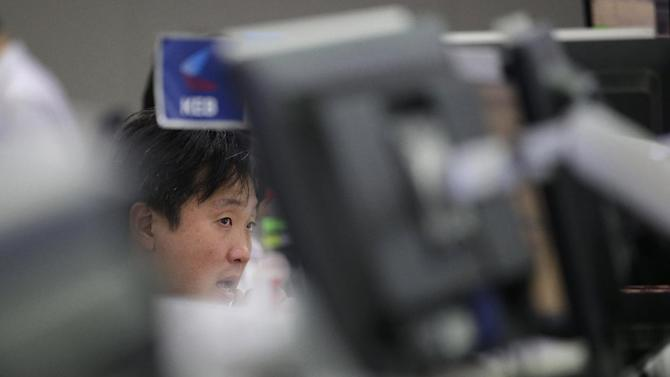 A currency trader watches computer screens at the foreign exchange dealing room of the Korea Exchange Bank headquarters in Seoul, South Korea, Tuesday, July 7, 2015. Chinese stocks fell Tuesday despite official efforts to shore up slumping prices while other Asian markets were mixed after Greece's spiraling crisis weighed on Wall Street. (AP Photo/Lee Jin-man)