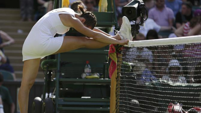 Jelena Jankovic of Serbia stretches during her match against Petra Kvitova of the Czech Republic at the Wimbledon Tennis Championships in London