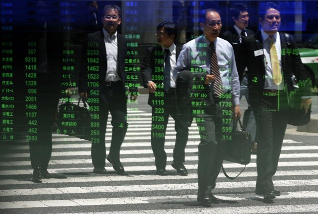 Passers-by are reflected on a stock quotation board at a brokerage in Tokyo