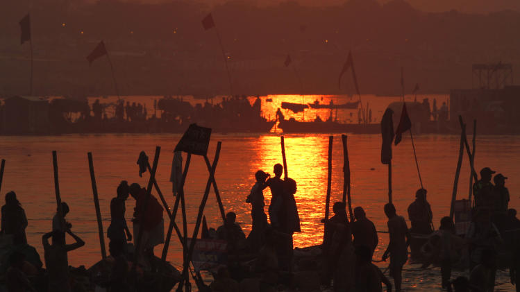 Hindu devotees pray against a setting sun, after a holy dip at 'Sangam', the confluence of Hindu holy rivers Ganges, Yamuna and the mythical Saraswati, during the Maha Kumbh festival at Allahabad, India, Sunday, Feb. 10, 2013.  Led by heads of monasteries arriving on chariots and ash-smeared naked ascetics, millions of devout Hindus plunged into the frigid waters of the holy Ganges River in India on Sunday in a ritual that they believe will wash away their sins. Sunday was the third of six auspicious bathing days during the Kumbh Mela, or Pitcher Festival, which lasts 55 days and is one of the world's largest religious gatherings. (AP Photo /Rajesh Kumar Singh)