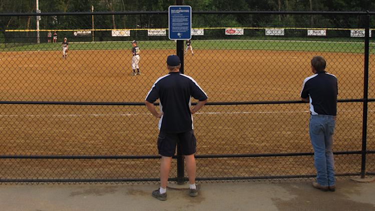 Coaches and parents watch a youth baseball game near a sign on a fence about parent behavior in Buffalo Grove, Ill. on Monday, June 10, 2013. Earlier in the month, park district officials in the Chicago suburb posted the signs asking parents to behave and keep the games in perspective. (AP Photo/Martha Irvine)