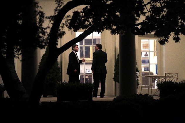 FILE - In this Wednesday, April 6, 2011 file photo, two U.S. Secret Service agents speak outside the Oval Office of the White House in Washington ahead of President Barack Obama's meeting with House S