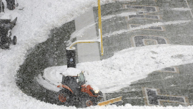 Ground crews try to clear falling snow from the field at Michie Stadium before the start of a NCAA college football game between Army and Fordham University in West Point, N.Y., Saturday, Oct. 29, 2011.  (AP Photo/Hans Pennink)