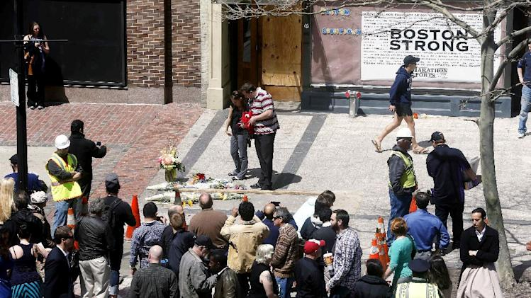 People gather at the site where the first bomb detonated on April 15 near the finish line of the Boston Marathon on Boylston Street in Boston, Wednesday, April 24, 2013. Traffic was allowed to flow all the way down Boylston Street on Wednesday morning for the first time since two explosions. (AP Photo/Michael Dwyer)