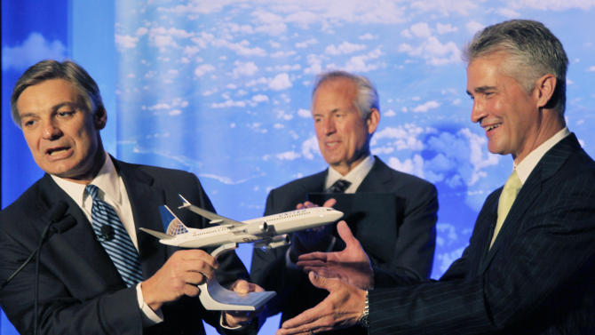 Boeing Commercial Airplanes CEO Ray Conner, presents a model of Boeing's new 737 Max 9 to United Airlines CEO Jeff Smisek during a news conference as Boeing CEO Jim McNerney looks on, Thursday, July 12, 2012, in Chicago. United Airlines and Boeing announce that United is buying 150 Boeing 737s, and is planning to use them to replace older planes that are not as fuel efficient. (AP Photo/M. Spencer Green)