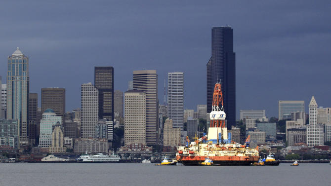 FILE - In this July 19, 2011, file photo, the floating oil-drilling rig Kulluk is seen briefly bathed in light as it passes an otherwise cloudy and dark downtown Seattle, including the 932-foot Columbia Center tower behind, while being moved by tugs to a maintenance facility. Seattle Mayor Ed Murray said Monday, May 4, 2015, the Port of Seattle can't host Royal Dutch Shell's offshore Arctic oil-drilling fleet unless it gets a new land-use permit. Shell has been hoping to base its fleet at the port's Terminal 5. Shell has argued that its planned activities at the terminal — such as docking, equipment loading and crew changes — are no more environmentally risky than loading or unloading shipping containers. (AP Photo/Elaine Thompson, File)