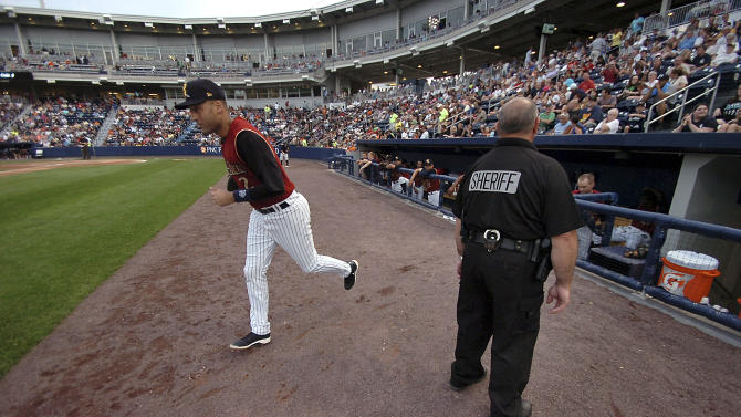 New York Yankees shortstop Derek Jeter runs onto the field next to a Lackawanna County sheriff's officer on Wednesday, July 10, 2013, during a rehab baseball game in Moosic, Pa., with the Scranton/Wilkes-Barre RailRiders against the Rochester Red Wings. (AP Photo/Scranton Times-Tribune, Butch Comegys) WILKES-BARRE TIMES-LEADER OUT MANDATORY CREDIT